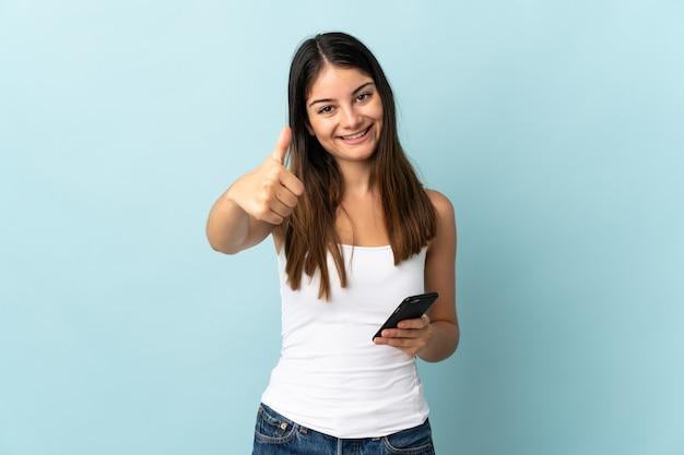 Jonge blanke vrouw met behulp van mobiele telefoon geïsoleerd op blauwe muur met duimen omhoog omdat er iets goeds is gebeurd