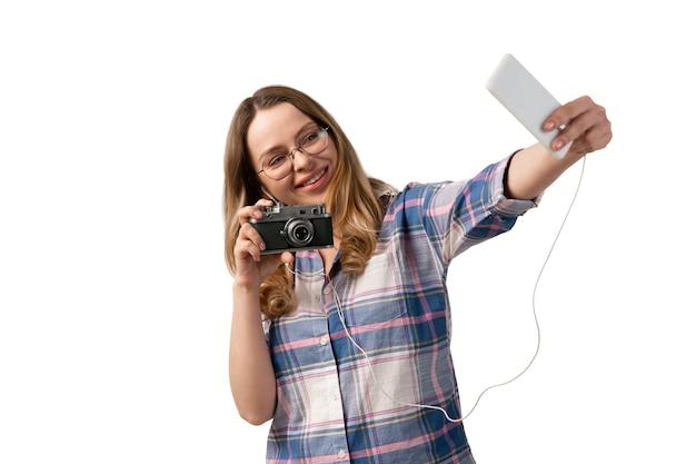 Jonge blanke vrouw met behulp van smartphone, apparaten, gadgets geïsoleerd op een witte muur. concept van moderne technologieën, gadgets, tech, emoties, advertentie. kopieerruimte. praten, ontmoeten online onderwijs.