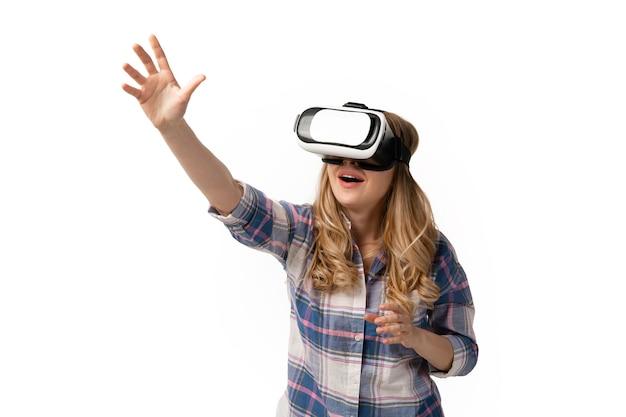 Jonge blanke vrouw met behulp van vr-headset-apparaten, gadgets geïsoleerd op een witte muur. concept van moderne technologieën, gadgets, tech, emoties, advertentie. kopieerruimte. gamen, online onderwijs ontmoeten.