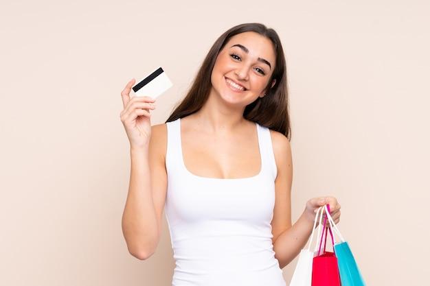 Jonge blanke vrouw met boodschappentassen en een creditcard