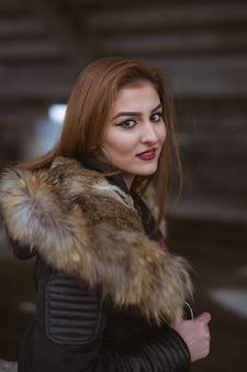 Jonge blanke vrouw met bruin haar die een zwarte jas draagt