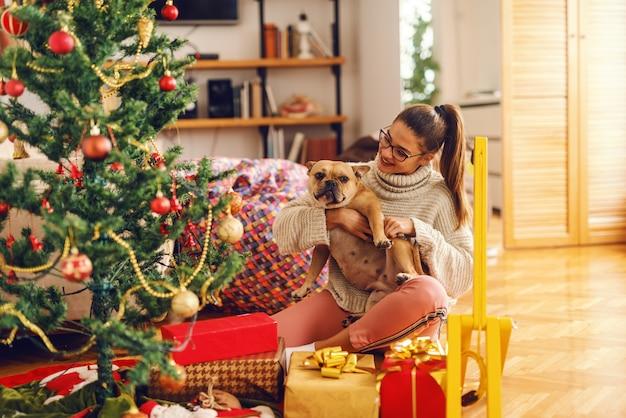 Jonge blanke vrouw met bruin haar haar hond aaien. naast hen kerstboom en geschenken. interieur, kerstvakantie concept.