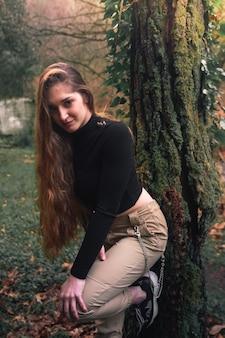Jonge blanke vrouw met casual kleding poseren in het bos.