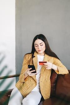 Jonge blanke vrouw met creditcard, met behulp van smartphone en online winkelen.