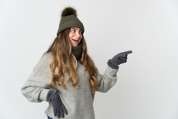 Jonge blanke vrouw met de winterhoed die op witte achtergrond wordt geïsoleerd die vinger naar de kant richt en een product voorstelt