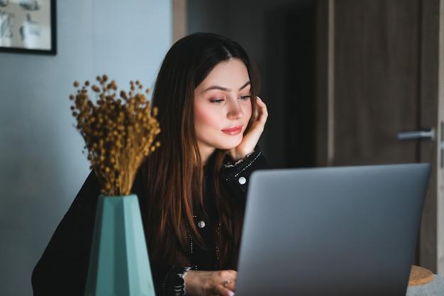 Jonge blanke vrouw met donkerbruin haar laptopcomputer gebruikt in de keuken thuis, tekst typen op het toetsenbord
