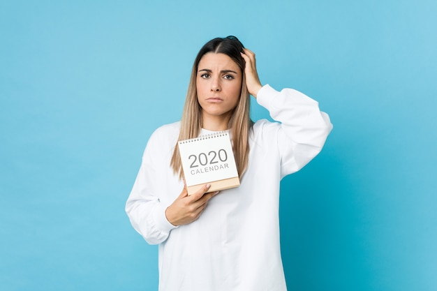 Jonge blanke vrouw met een 2020-kalender die geschokt is, heeft ze een belangrijke vergadering onthouden.