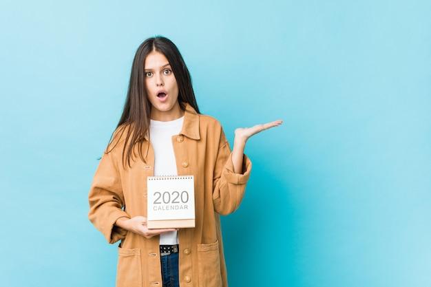 Jonge blanke vrouw met een 2020 kalender onder de indruk te houden kopie ruimte op palm.