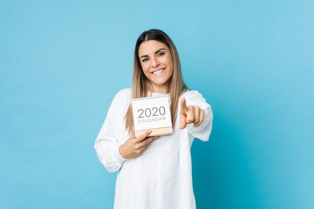 Jonge blanke vrouw met een 2020 kalender vrolijke glimlach wijzend naar de voorkant.