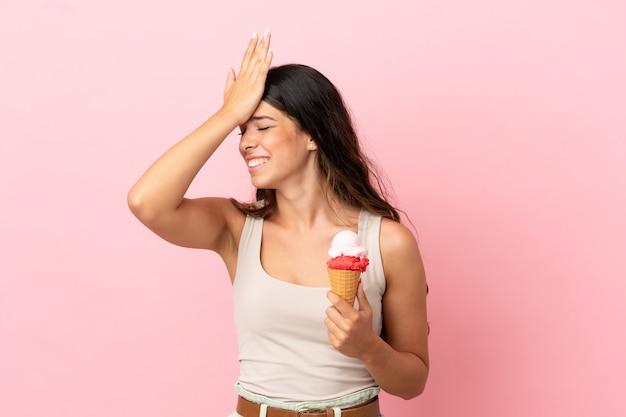 Jonge blanke vrouw met een cornet-ijsje geïsoleerd op roze achtergrond heeft iets gerealiseerd en is van plan de oplossing