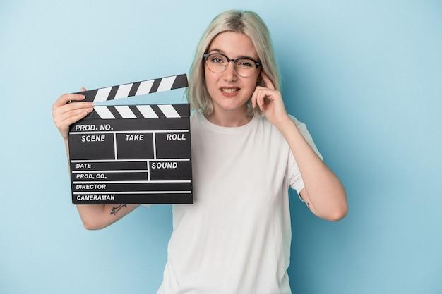 Jonge blanke vrouw met een filmklapper geïsoleerd op een blauwe achtergrond die oren bedekt met handen.