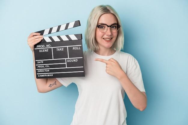 Jonge blanke vrouw met een filmklapper geïsoleerd op een blauwe achtergrond glimlachend en opzij wijzend, met iets op lege ruimte.