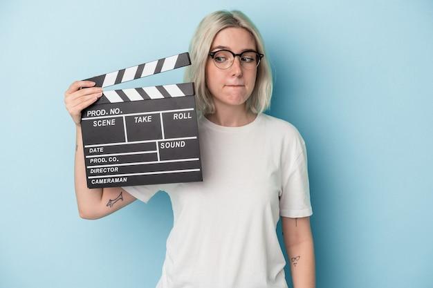 Jonge blanke vrouw met een filmklapper geïsoleerd op een blauwe achtergrond verward, voelt zich twijfelachtig en onzeker.
