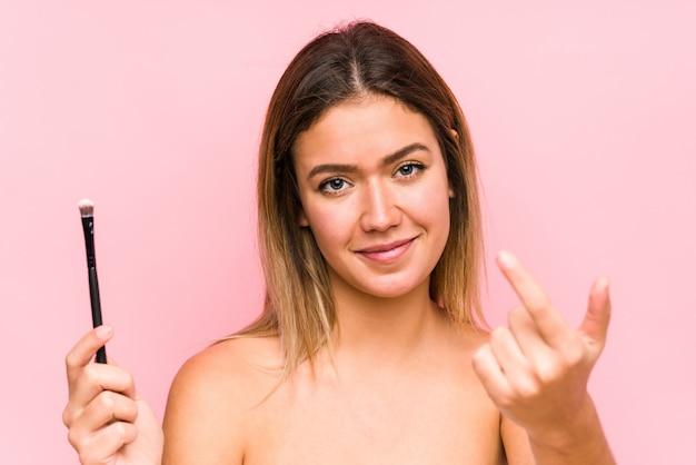 Jonge blanke vrouw met een geïsoleerde wenkbrauw wijzend met de vinger naar je alsof uitnodigend dichterbij komen.