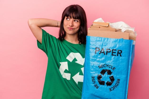 Jonge blanke vrouw met een gerecycleerde kartonnen zak geïsoleerd op roze achtergrond achterhoofd aanraken, denken en een keuze maken.