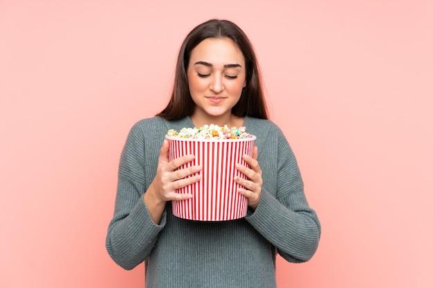 Jonge blanke vrouw met een grote emmer popcorn