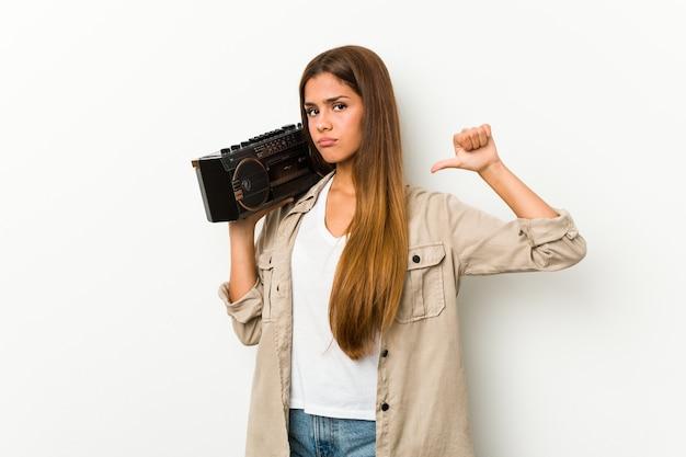 Jonge blanke vrouw met een guettoblaster voelt zich trots en zelfverzekerd, voorbeeld om te volgen.
