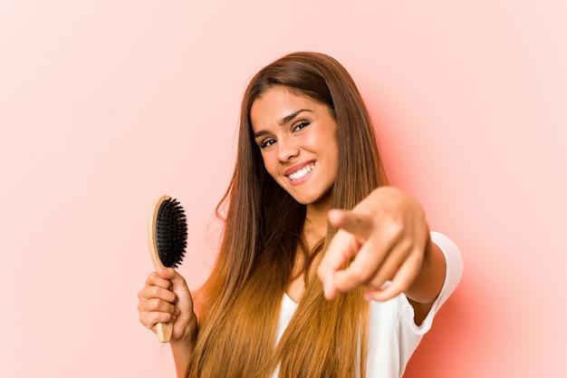 Jonge blanke vrouw met een haarborstel vrolijke glimlach wijzend naar de voorkant.