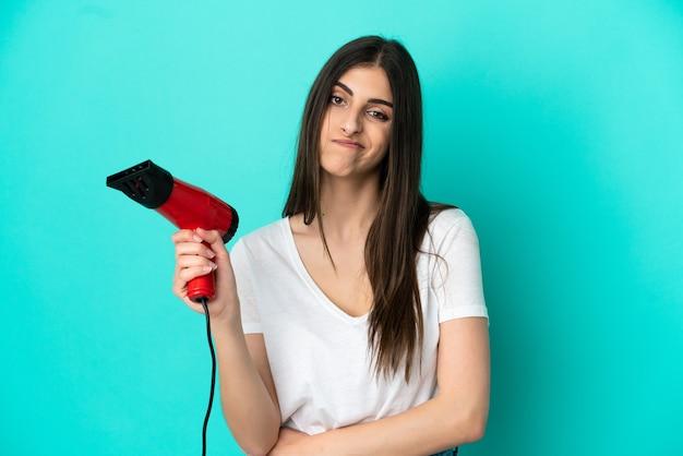 Jonge blanke vrouw met een haardroger geïsoleerd op blauwe achtergrond met droevige uitdrukking