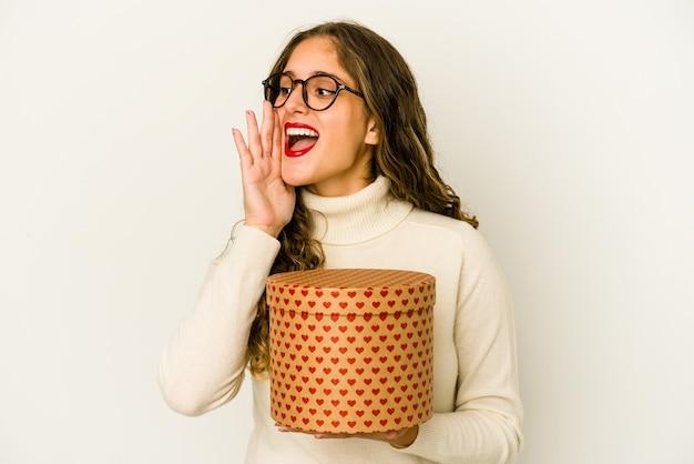 Jonge blanke vrouw met een hart valentijnsdag doos geïsoleerd schreeuwen en met palm in de buurt van geopende mond.