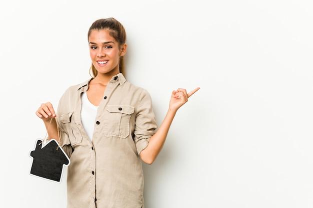 Jonge blanke vrouw met een huisje glimlachend vrolijk wijzend met wijsvinger weg.