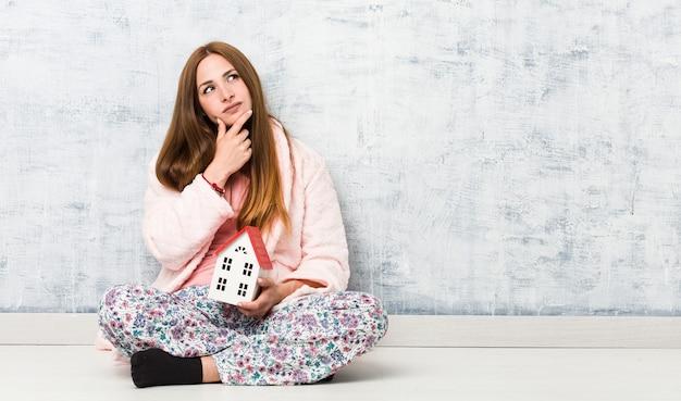 Jonge blanke vrouw met een huisje opzij kijkend met een twijfelachtige en sceptische uitdrukking.