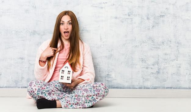 Jonge blanke vrouw met een huispictogram verrast wijzend op zichzelf, breed glimlachend.