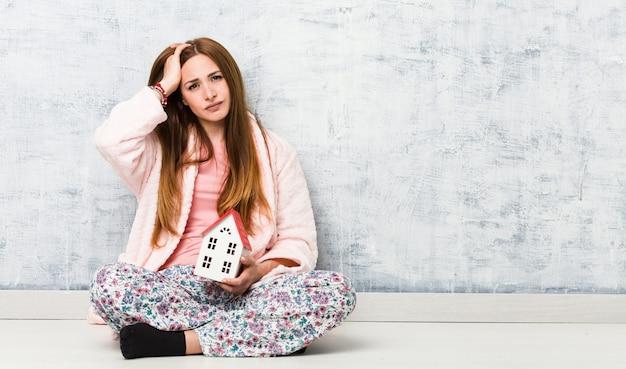 Jonge blanke vrouw met een huispictogram wordt geschokt, ze heeft belangrijke vergadering onthouden.