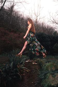 Jonge blanke vrouw met een kleurrijke jurk midden in het bos naast een riviertje Premium Foto