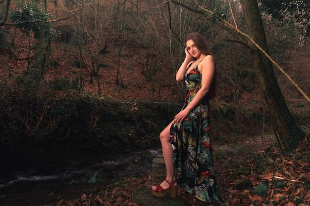 Jonge blanke vrouw met een kleurrijke jurk midden in het bos naast een riviertje