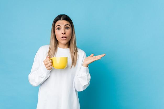 Jonge blanke vrouw met een koffiekopje onder de indruk houden kopie ruimte op palm.