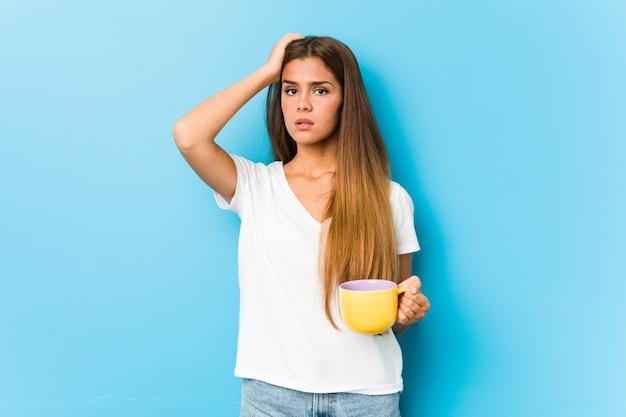 Jonge blanke vrouw met een koffiemok wordt geschokt, ze heeft belangrijke vergadering onthouden.