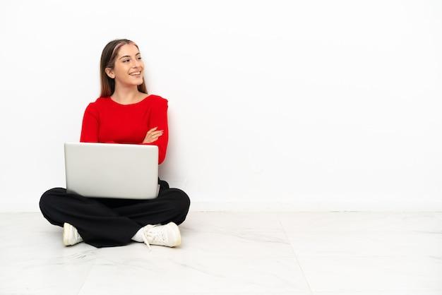 Jonge blanke vrouw met een laptop zittend op de vloer gelukkig en glimlachend