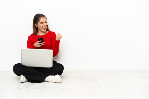 Jonge blanke vrouw met een laptop zittend op de vloer met telefoon in overwinningspositie