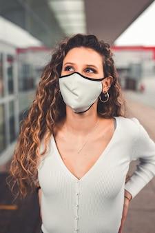 Jonge blanke vrouw met een masker in een stedelijk gebied