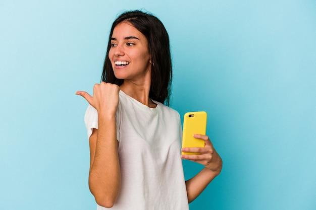 Jonge blanke vrouw met een mobiele telefoon geïsoleerd op blauwe achtergrond wijst met duimvinger weg, lachend en zorgeloos.