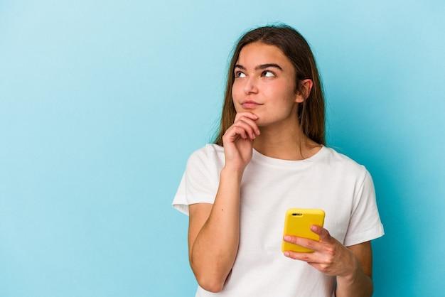 Jonge blanke vrouw met een mobiele telefoon geïsoleerd op blauwe achtergrond zijwaarts kijkend met twijfelachtige en sceptische uitdrukking.