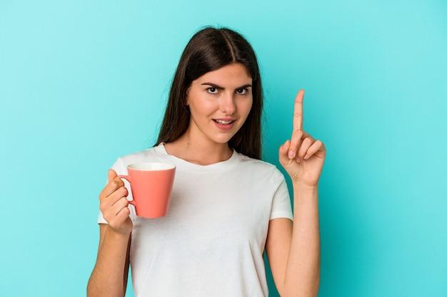 Jonge blanke vrouw met een mok geïsoleerd op blauwe achtergrond met een idee, inspiratie concept.