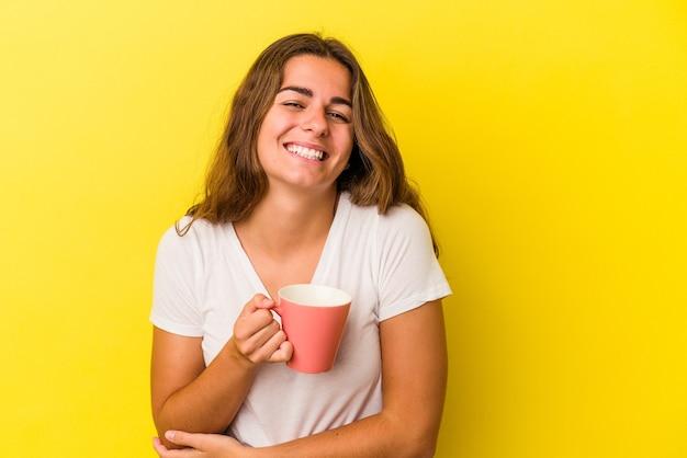 Jonge blanke vrouw met een mok geïsoleerd op gele achtergrond lachen en plezier maken.