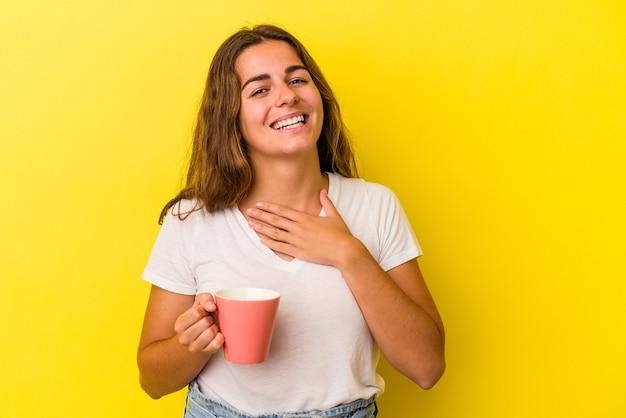 Jonge blanke vrouw met een mok geïsoleerd op gele achtergrond lacht hardop terwijl ze de hand op de borst houdt.