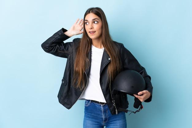 Jonge blanke vrouw met een motorhelm geïsoleerd op blauw luisteren naar iets door hand op het oor te leggen