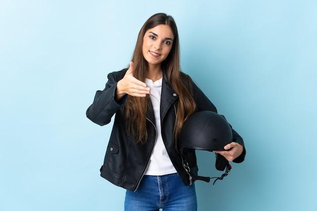 Jonge blanke vrouw met een motorhelm geïsoleerd op blauwe handen schudden voor het sluiten van een goede deal