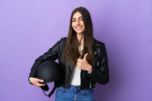Jonge blanke vrouw met een motorhelm geïsoleerd op een paarse achtergrond met een duim omhoog gebaar