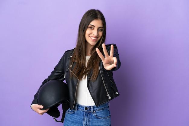 Jonge blanke vrouw met een motorhelm geïsoleerd op paarse achtergrond gelukkig en drie tellen met vingers