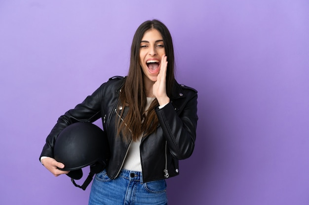 Jonge blanke vrouw met een motorhelm geïsoleerd op paarse achtergrond schreeuwen met wijd open mond