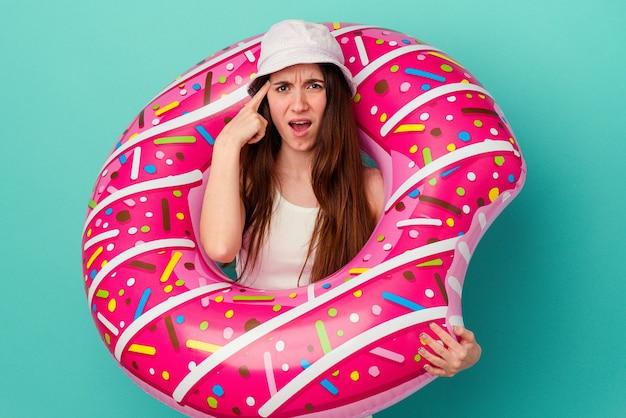 Jonge blanke vrouw met een opblaasbare donut geïsoleerd op blauwe achtergrond met een teleurstelling gebaar met wijsvinger.