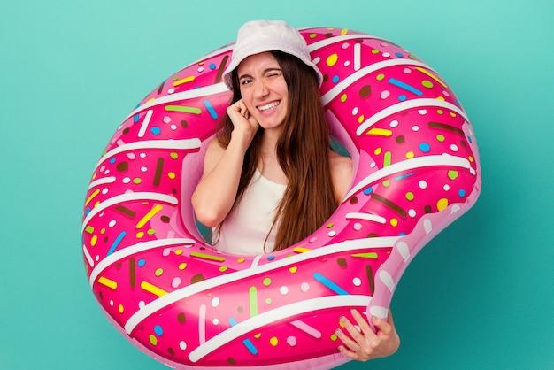 Jonge blanke vrouw met een opblaasbare donut geïsoleerd op een blauwe achtergrond die oren bedekt met handen.