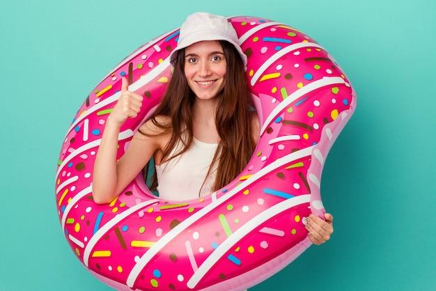 Jonge blanke vrouw met een opblaasbare donut geïsoleerd op een blauwe achtergrond glimlachend en duim omhoog raising