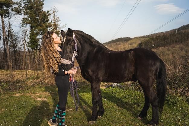 Jonge blanke vrouw met een paard in een manege