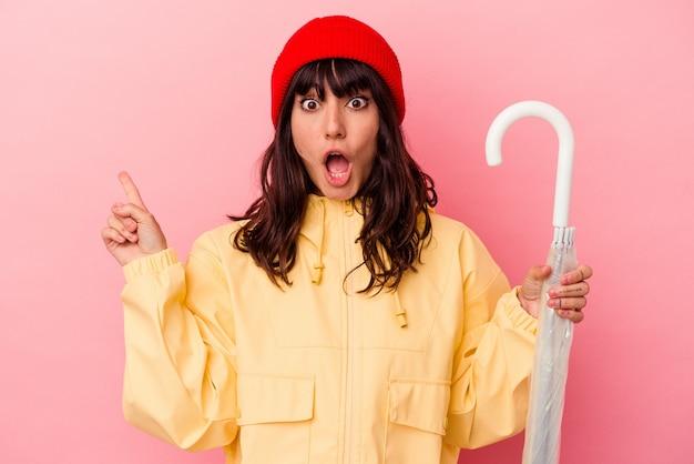 Jonge blanke vrouw met een paraplu geïsoleerd op een roze achtergrond die naar de zijkant wijst